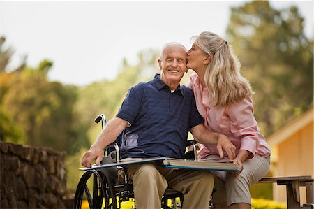 Smiling mature woman looking through a photo album with her senior husband. Stock Photo - Premium Royalty-Free, Code: 6128-08738392