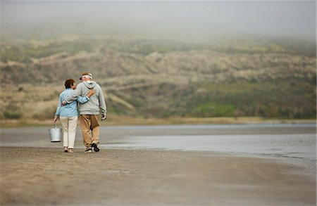 Happy senior couple walking together on a beach. Stock Photo - Premium Royalty-Free, Code: 6128-08738324