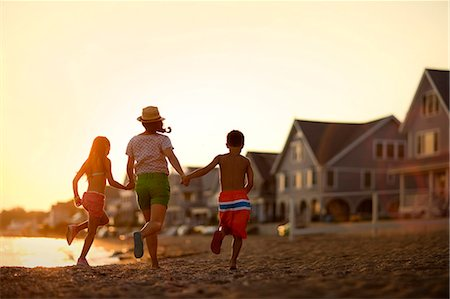 preteen boy shirtless - Mother and her two children holding hands and running on the beach at sunset. Stock Photo - Premium Royalty-Free, Code: 6128-08738480