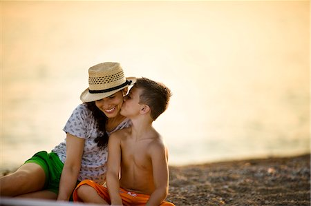 preteen kissing - Boy kisses his mother's cheek  on the beach at sunset. Stock Photo - Premium Royalty-Free, Code: 6128-08738482