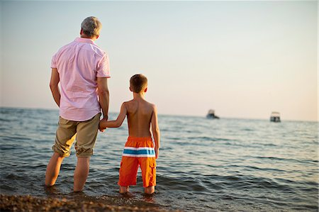 preteen boy shirtless - Grandfather holds his grandson's hand as they stand in the water and look out at the ocean. Stock Photo - Premium Royalty-Free, Code: 6128-08738491