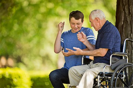 Smiling teenage boy playing rock paper scissors with his grandfather. Stock Photo - Premium Royalty-Free, Code: 6128-08738403