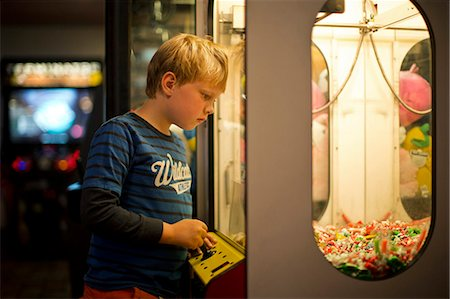 Young boy looking at an arcade game. Stock Photo - Premium Royalty-Free, Code: 6128-08738407