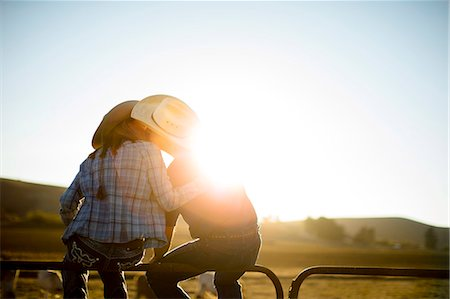 Farmer and his wife sitting on a fence at their ranch and kissing at sunset. Stock Photo - Premium Royalty-Free, Code: 6128-08738555