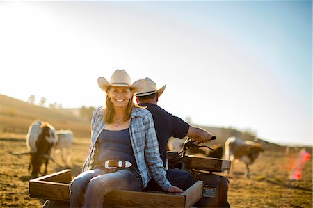 Portrait of a woman riding on the back of her husband's quad bike out on the ranch. Stock Photo - Premium Royalty-Free, Code: 6128-08738561