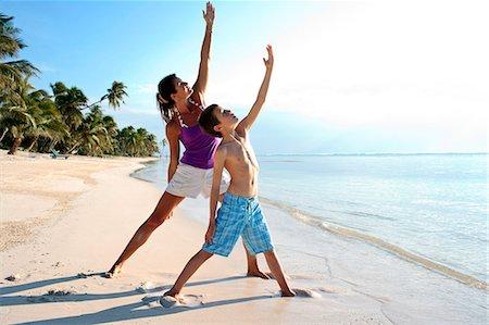 preteen boy shirtless - Mid-adult woman and her son practicing yoga together on a sandy tropical beach. Stock Photo - Premium Royalty-Free, Code: 6128-08841046