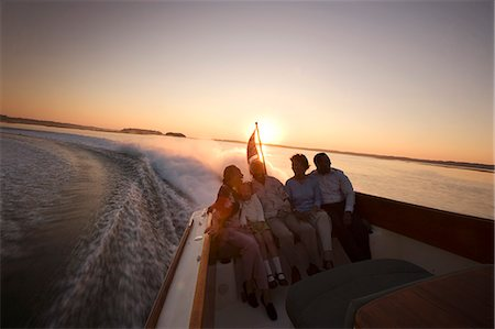 Happy family sitting in the back of a jet boat on the water at sunset. Stock Photo - Premium Royalty-Free, Code: 6128-08825421