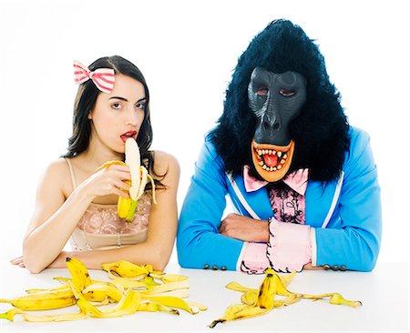 Woman Eating Banana Next to Sad Gorilla Man Stock Photo - Premium Royalty-Free, Code: 613-07067842