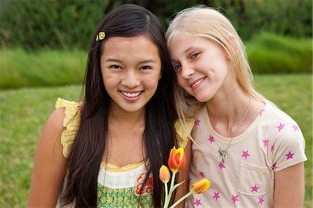 Teenage girls in garden, portrait, smiling Stock Photo - Premium Royalty-Free, Code: 613-07067892