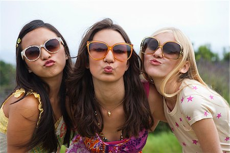 sunglasses - Teenage girls in garden blowing kisses Stock Photo - Premium Royalty-Free, Code: 613-07067944