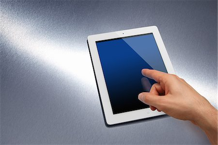 Electronic tablet device on brushed metal Stock Photo - Premium Royalty-Free, Code: 613-07068349