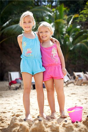 girls standing in front of sand castle on beach Stock Photo - Premium Royalty-Free, Code: 613-07454000