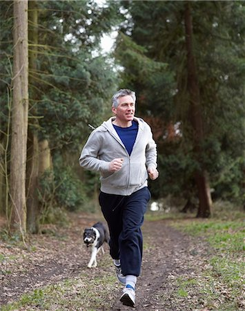 Man running in woodland with dog. Stock Photo - Premium Royalty-Free, Code: 613-07454431