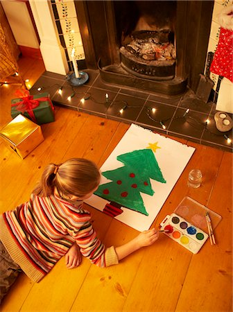 sweater and fireplace - Girl painting christmas tree in front of fire. Stock Photo - Premium Royalty-Free, Code: 613-07458935