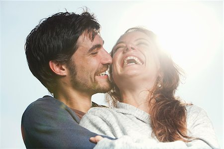 Young couple laughing together, hugging outdoors Stock Photo - Premium Royalty-Free, Code: 613-07459085