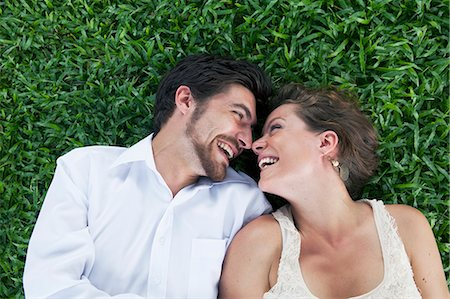 Young couple smiling at each other on the grass Stock Photo - Premium Royalty-Free, Code: 613-07459090