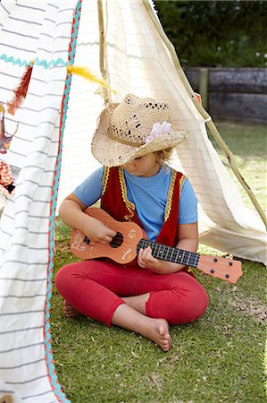 Girl playing guitar in a toy tent Stock Photo - Premium Royalty-Free, Code: 613-07459158