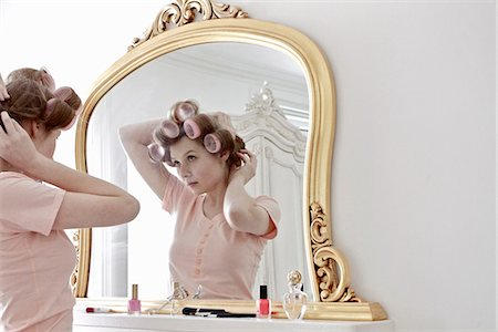 Woman putting curlers in her hair Stock Photo - Premium Royalty-Free, Code: 613-07459195