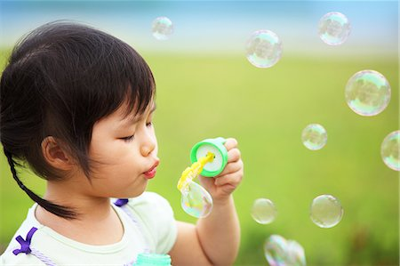 Little Girl Blowing Bubbles Stock Photo - Premium Royalty-Free, Code: 613-07459600