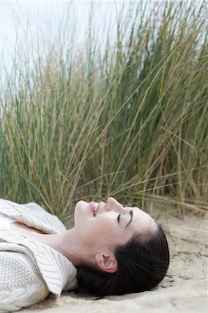 Woman laying with eyes closed at beach. Stock Photo - Premium Royalty-Free, Code: 613-07459690