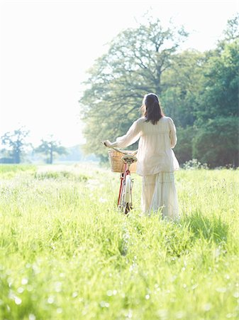 Woman walking with bicycle through Summer meadow. Stock Photo - Premium Royalty-Free, Code: 613-07492584