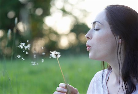 Profile of woman blowing dandelion. Stock Photo - Premium Royalty-Free, Code: 613-07492583
