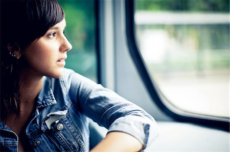 Young woman looking out tram window Stock Photo - Premium Royalty-Free, Code: 613-07492657