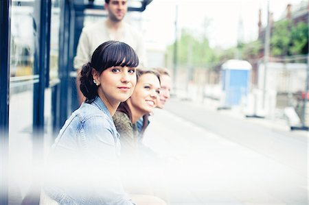 Four young adults sitting at tram station Stock Photo - Premium Royalty-Free, Code: 613-07492662