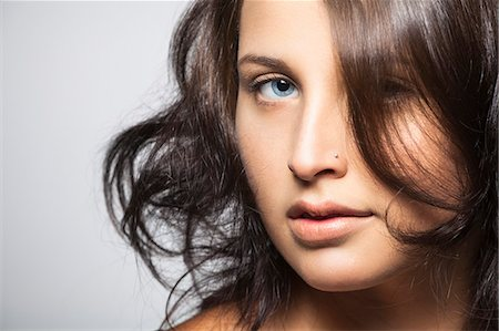 Portrait of young woman with piercing in nose Stock Photo - Premium Royalty-Free, Code: 613-07492712
