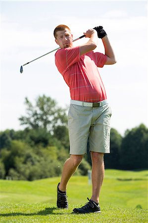 swing (sports) - A man hitting a golf ball. Stock Photo - Premium Royalty-Free, Code: 613-07492737