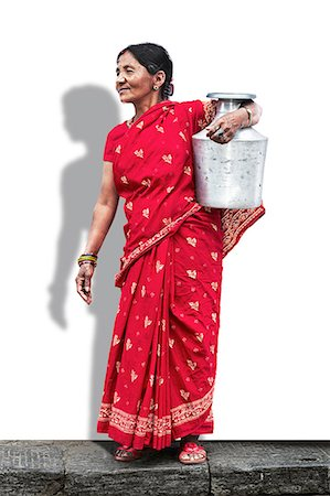 Lady in red saree carrying a bucket of water Stock Photo - Premium Royalty-Free, Code: 613-07492797