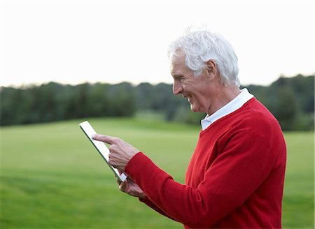 Profile of senior man using tablet on golf course. Stock Photo - Premium Royalty-Free, Code: 613-07596942