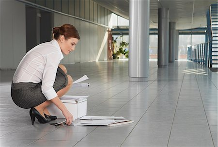 Businesswoman picking up papers in office corridor Stock Photo - Premium Royalty-Free, Code: 613-07673941