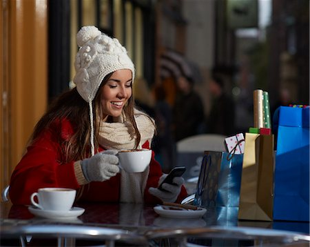europe coffee shop - Christmas shopper using phone at coffee shop. Stock Photo - Premium Royalty-Free, Code: 613-07673968
