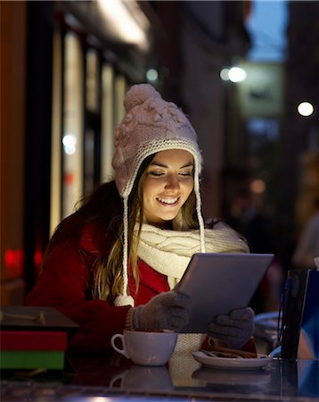europe coffee shop - Christmas shopper using tablet at coffee shop. Stock Photo - Premium Royalty-Free, Code: 613-07673970