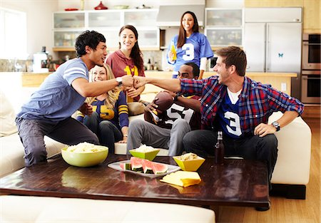 Friends watching football in living room. Stock Photo - Premium Royalty-Free, Code: 613-07767486