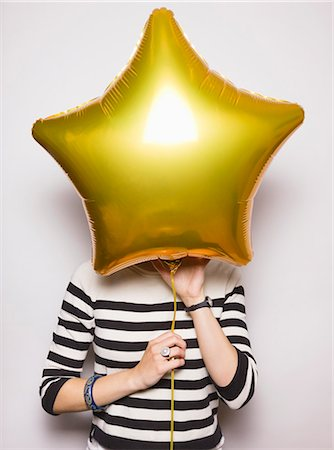 stars on white background - Young woman with face covered by balloon Stock Photo - Premium Royalty-Free, Code: 613-07780235