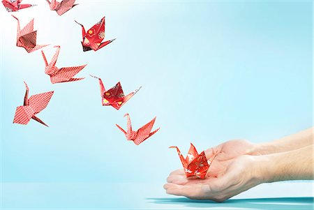 release - Red origami cranes flying away from hands Stock Photo - Premium Royalty-Free, Code: 613-07780666
