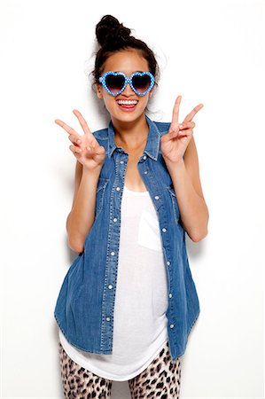 Teenage girl peace signs in heart shape glasses Stock Photo - Premium Royalty-Free, Code: 613-07780739