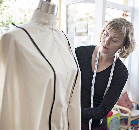 Designer pins fabric on dress form Stock Photo - Premium Royalty-Free, Code: 613-07780795