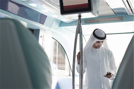 Arab man in traditional dress using metro in Dubai Stock Photo - Premium Royalty-Free, Code: 613-07780913