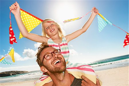Daughter (6-8) sitting on father's shoulders, smil Stock Photo - Premium Royalty-Free, Code: 613-07845132