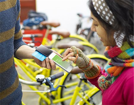 person on phone with credit card - Woman using mobile payment device in bike shop. Stock Photo - Premium Royalty-Free, Code: 613-07845155