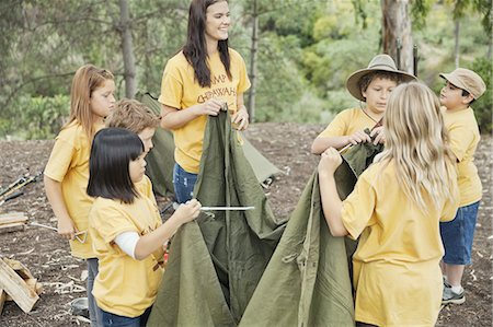 Camp counsellor and young campers setting up canvas tent Stock Photo - Premium Royalty-Free, Code: 613-07848165