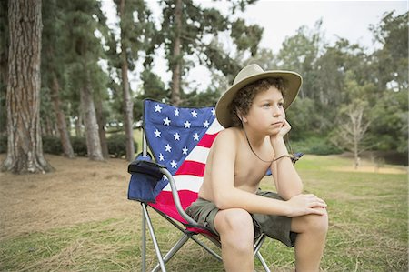 Young boy sitting on folding chair while looking away in forest Stock Photo - Premium Royalty-Free, Code: 613-07848228