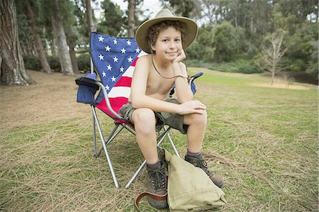 Portrait of boy sitting on folding chair in forest Stock Photo - Premium Royalty-Free, Code: 613-07848229