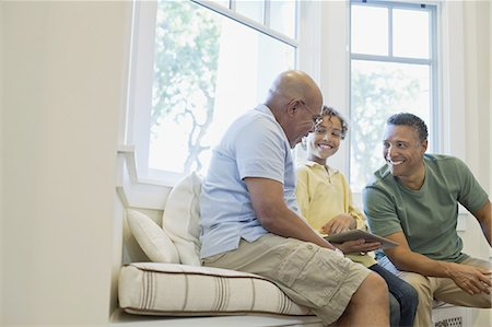Happy boy with father and grandfather sharing digital tablet on sofa Stock Photo - Premium Royalty-Free, Code: 613-07848290