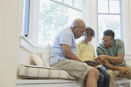 Happy boy with father and grandfather sharing digital tablet on sofa Stock Photo - Premium Royalty-Free, Code: 613-07848291