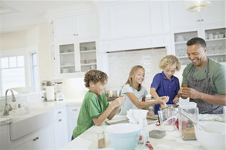 Family preparing cookies at kitchen counter Stock Photo - Premium Royalty-Free, Code: 613-07848328