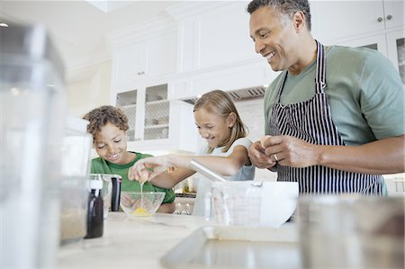 Happy father with children breaking eggs together in kitchen Stock Photo - Premium Royalty-Free, Code: 613-07848321